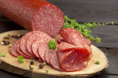 halved in slices salami served on a slice of wood with thyme and ground pepper Reklamní fotografie