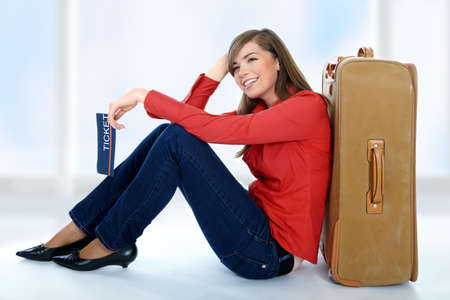 Tourist girl sitting on a suitcase with a ticket in her hand Stock Photo