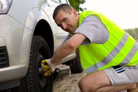 Man changing a wheel in his car Stock Photo - 4097456