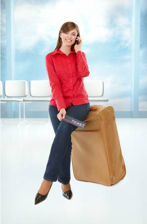 Tourist girl sitting on a suitcase with a ticket in her hand and mobile phone Stock Photo