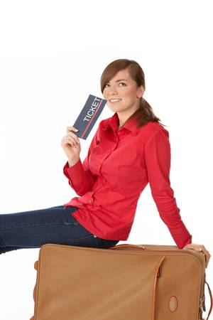 boarding card: Turistiche ragazza seduta su una valigia con un biglietto in mano Archivio Fotografico
