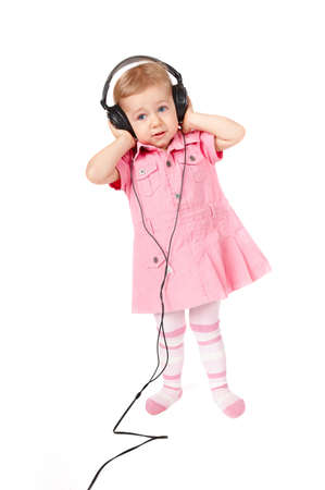 Portrait of young baby girl listening music via phones and dancing photo