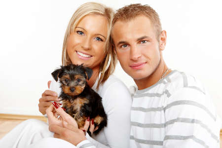 Happy couple with a funny puppy of Yorkshire Terrier photo