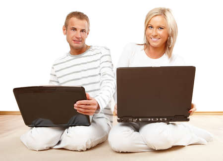 Portrait of a happy couple sitting on the floor with laptop photo