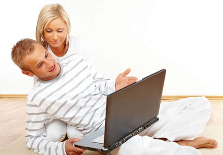 Portrait of a talking couple sitting on the floor with laptop photo