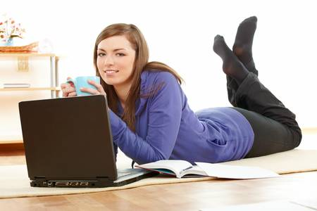 lying on floor: Young pretty women relaxing and using laptop computer