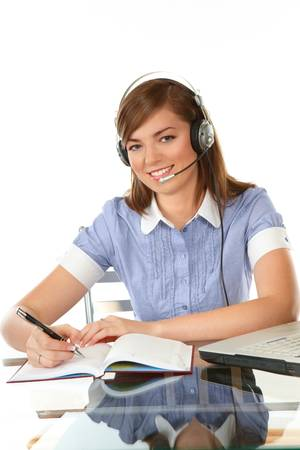 Woman in office with headset, laptop writing notes photo