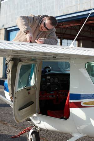 checking in: Pilot doing preflight checking in his plane Stock Photo