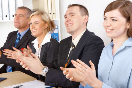 admire: Smiling business group clapping hands at the meeting