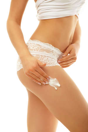 Woman applying cosmetic moisturizer cream on body