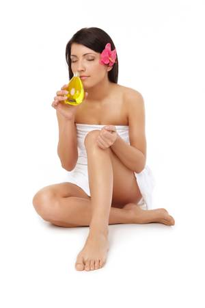 Beautiful woman with towel smelling perfume photo