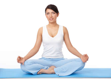 Portrait of fit young woman doing yoga exercise on blue mat, isolated on white photo