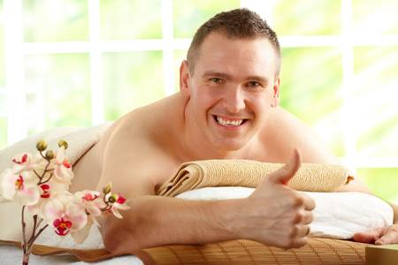 Man resting in sunny spa salon laying on the mat and showing how happy he is by thumb up gesture with flowers photo