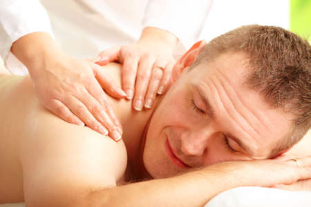 Male enjoying massage treatment with female hands on his shoulder and back photo