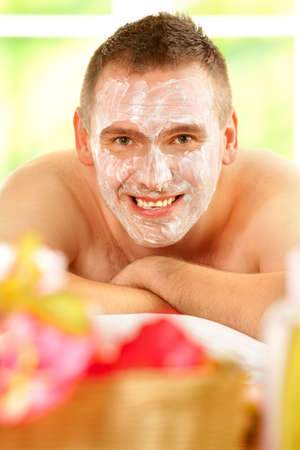 Happy man resting in sunny spa salon laying with facial mask Stock Photo - 6435828