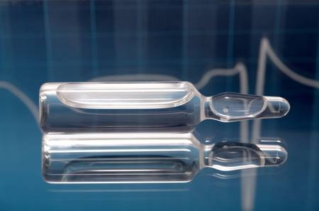 Glass ampules filled with medicine and EKG in background photo