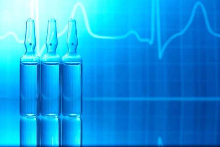 ampoules: Ampules filled with medicine and EKG in background
