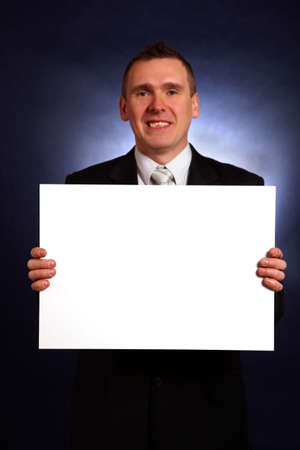 Smiling businessman holding a big blank card. Stock Photo - 6470571