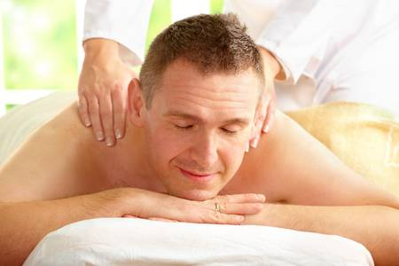 Male enjoying massage treatment with female hands on his shoulder and back Stock Photo - 6482381