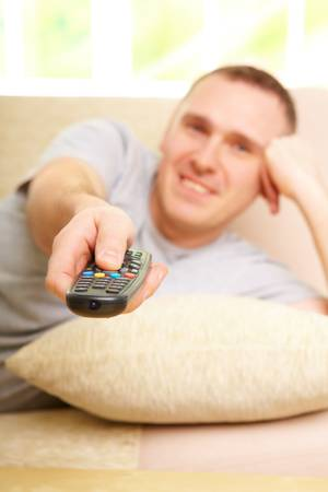 Relaxed handsome man smiling lying on sofa with remote control handheld, watching television in home Stock Photo - 6482382