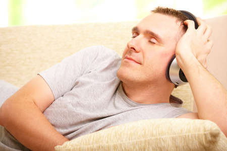Relaxed man listening music with headphones laying on sofa at home and smiling. Stock Photo - 6482385