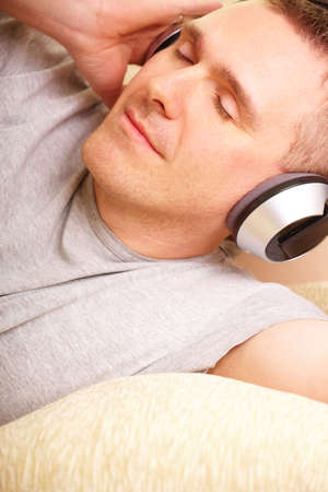 Close-up of face relaxed man listening music with headphones laying on sofa at home and gently smiling.