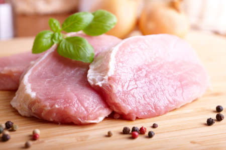 cutlets: Fresh raw pork chops on wooden cutting board with  pepper and basil Stock Photo