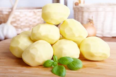 papas: Pila de papas frescas con verdes hojas de albahaca