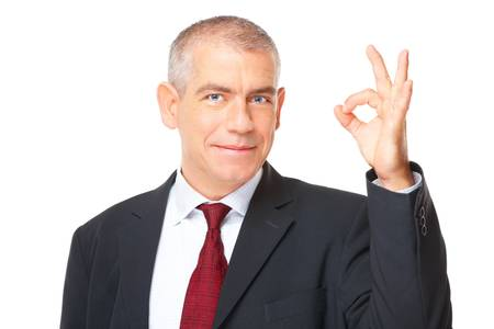 Happy mature businessman showing ok sign, meaning success in business    photo