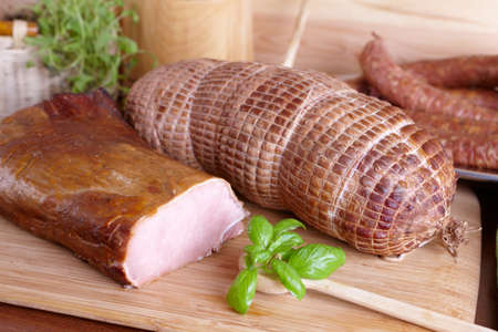 loin: Natural prepared slow food smoked pork sirloin, cured pork shoulder which looks similar to ham and ring-shaped sausage in the background all on the wooden board with herbs Stock Photo