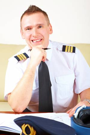 log book: Airline pilot wearing hat, shirt with epaulets and tie filling in and checking papers flight plan, weather forecast. Headset on the table.