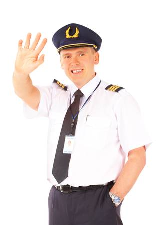 Cheerful airline pilot wearing uniform with epaulettes and hat waving, standing isolated on white background.  photo