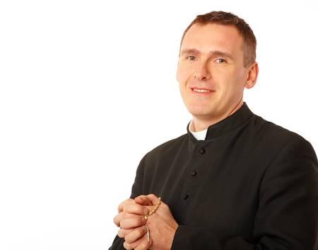 Vrolijke jonge priester met rozenkrans in zijn handen Stockfoto