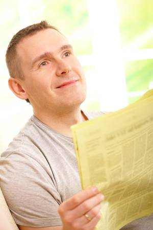hansome: Hansome man reading newspaper, sitting on couch at home and smiling