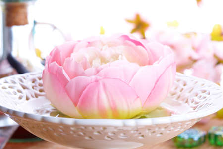 Tradicional alternative theraphy or medicine, also concept of healthy lifestyle, aromatherapy. Photo could be also used to illustrate a table decoration. Flower in liquid placed in beautiful bowl. photo