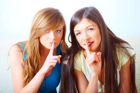 Two beautiful young girls gesturing for quiet with fingers over mouth shushing. Conceptual image illustrating secret or mystery