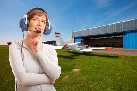 Cheerful woman pilot with headset used in aircraft standing on airfield, with airplane and hangar in the background
