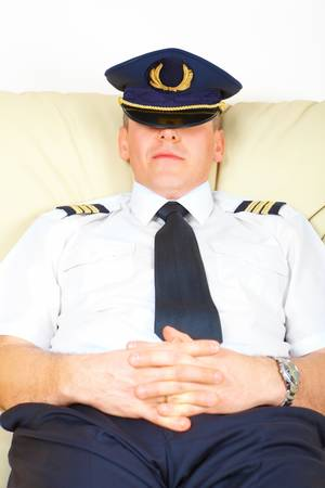 air crew: Commercial pilot wearing uniform with epaulettes and hat half sitting idly, resting or stiking.