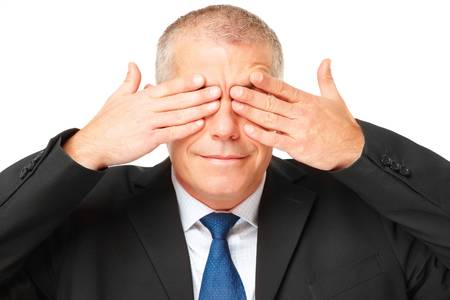 Face of gently smiling mature business man covering eyes with hands, isolated over white background photo