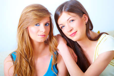 Two beautiful girls sitting on sofa in home with faces close to each other