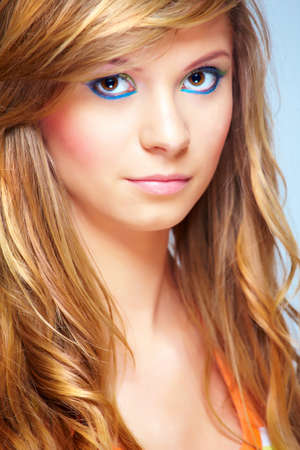 Portrait of young woman face with long blond hair and beautiful modern make-up. photo
