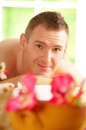 Man resting in sunny spa salon laying on the mat with flowers photo