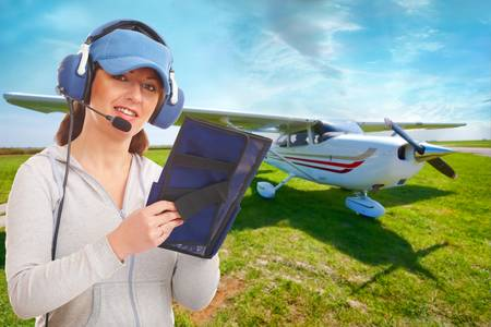 Cheerful woman pilot with headset used in aircraft taking notes on knee-pad, with airplane in the background