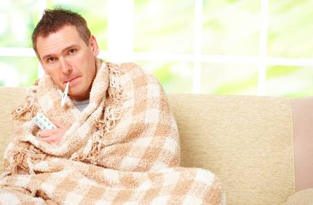 Man with cold sitting on sofa with thermometer in mouth photo