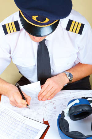 flight crew: Airline pilot wearing hat, shirt with epaulets and tie filling in and checking papers flight plan, log book and weather forecast. Headset on the table.