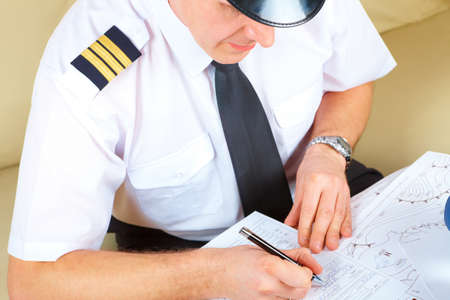 Smiling airline pilot wearing hat, shirt with epaulets and tie with pen in hand ready to filling in and checking papers flight plan, log book. Pilot is sitting in AIS ARO Air Traffic Services Reporting Office