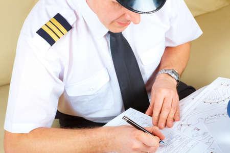 piloto de avion: Sonriente sombrero llevaba piloto de la aerol�nea, con charreteras camisa y corbata con l�piz en la mano listo para rellenar y comprobaci�n de plan de vuelo de documentos, libro de registro. Piloto est� sentado en la Oficina AIS ARO aire tr�fico servicios de informes Foto de archivo