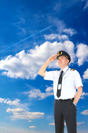 airline uniform: Cheerful airline pilot wearing uniform with epauletes and hat looking upwards, standing over a beautiful blue cloudy sky with flying jet airplane.