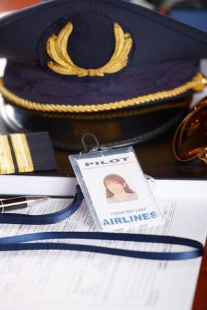 Professional airline pilot hat and id holder with epaulets and sun glasses laying on log book and flight plan. Stock Photo - 8887418