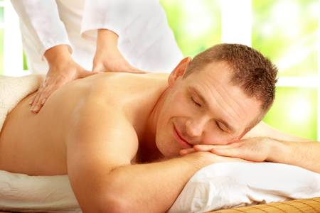 Male enjoying massage treatment with female hands on his back photo